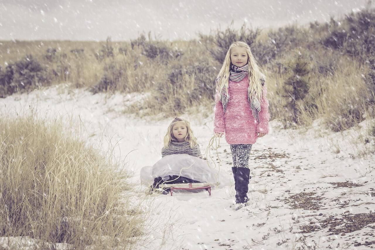 Sisters in the snow wearing wooden Scarves & Jumpers